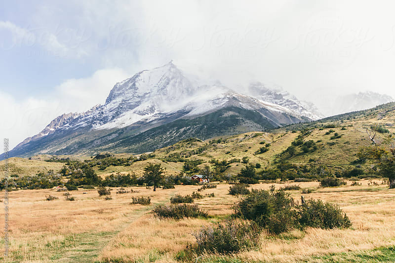 Mountain with snow covered in clouds and dry landscape in Torres del Paine, Chile, Patagonia by Alejandro Moreno de Carlos for Stocksy United