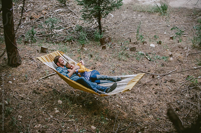 Couple in love laying on hammock in forest by Kristin Rogers Photography for Stocksy United