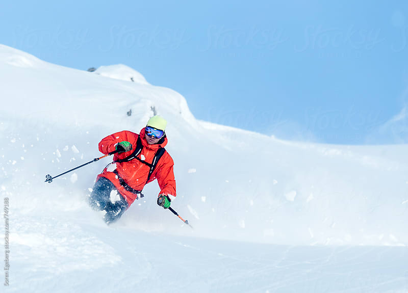 Skier in red jacket skiing powder snow in the mountains by Soren Egeberg for Stocksy United