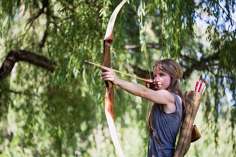Young woman aiming bow and arrow in the nature by michela ravasio for Stocksy United