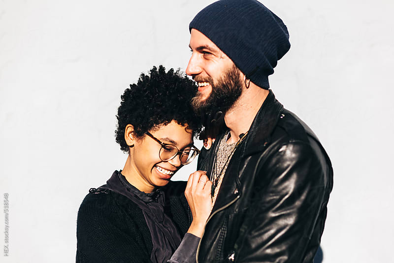 Young Smiling Couple Against A White Wall by HEX. for Stocksy United