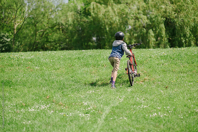 Boy pushes his bike up a grass embankment by Rebecca Spencer for Stocksy United