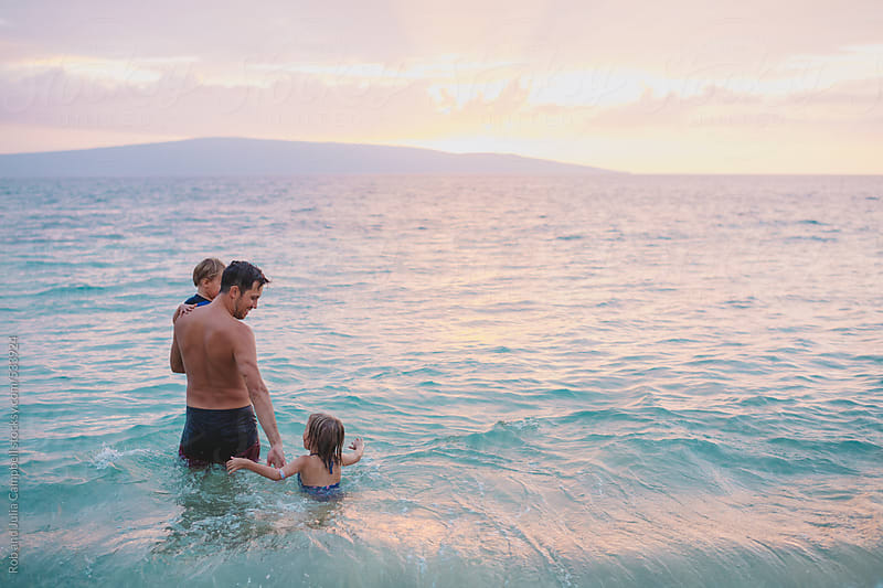 Young dad having fun with his kids on tropical beach at sunset by Rob and Julia Campbell for Stocksy United