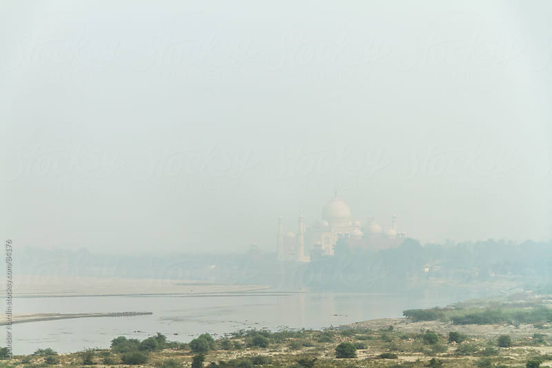taj mahal on the river yamuna descends into smog by Leander Nardin for Stocksy United