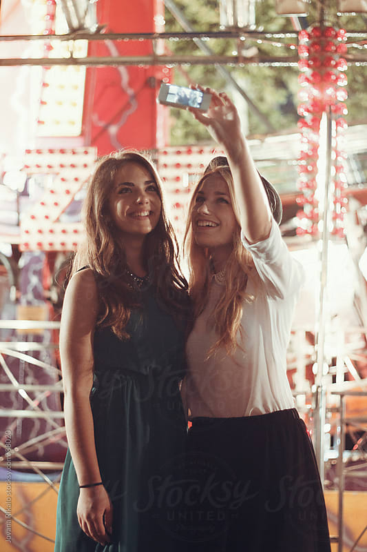 Girls having fun and taking pictures on carnival by Jovana Rikalo for Stocksy United