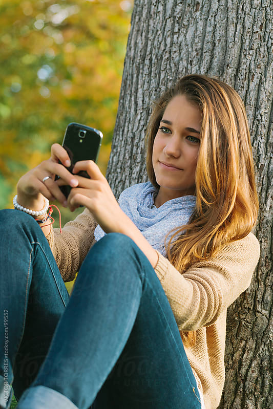Cute Teenager Using a Cell Phone in the Park by VICTOR TORRES for Stocksy United