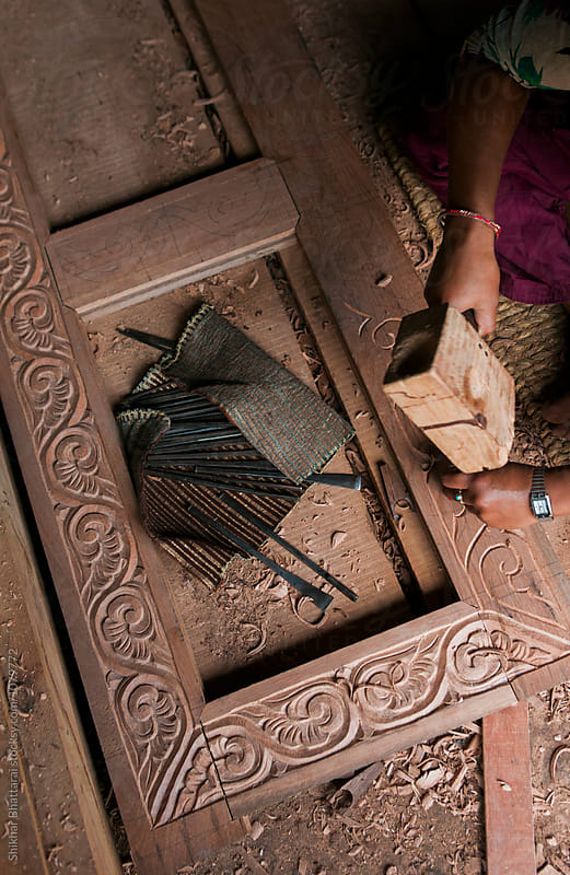An artist carving a wooden door frame. by Shikhar Bhattarai for Stocksy United