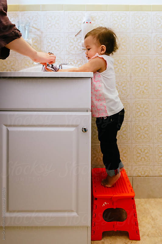Toddler learning to wash hands by Jen Grantham for Stocksy United