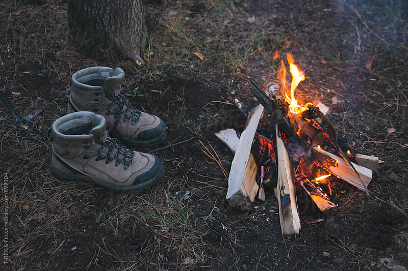 Man's boots near campfire by T-REX & Flower for Stocksy United