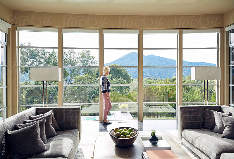 Mature woman relaxing in luxury home living room with view by Trinette Reed for Stocksy United