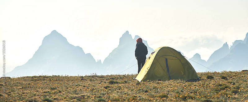 A tent and camper in a grass field on top of a mountain with big sharp mountains in the background. by Jacques van Zyl for Stocksy United