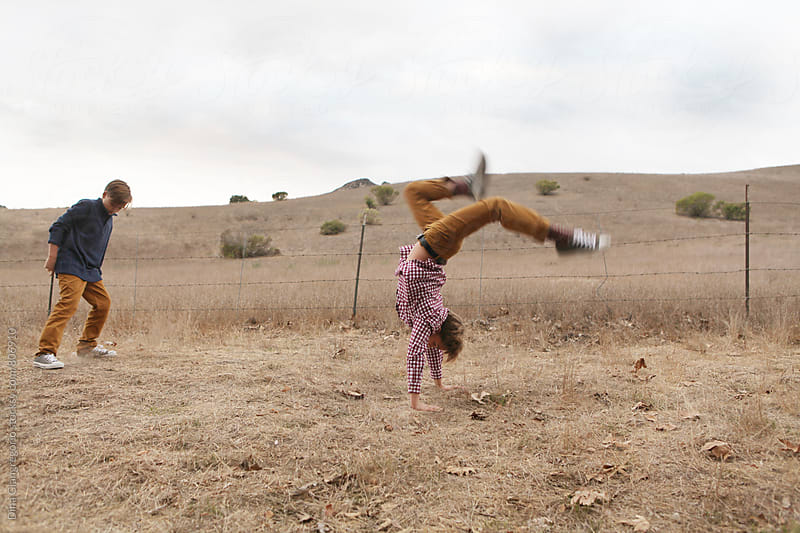 Boy Doing Hand Stand With Other Boy Nearby  by Dina Giangregorio for Stocksy United