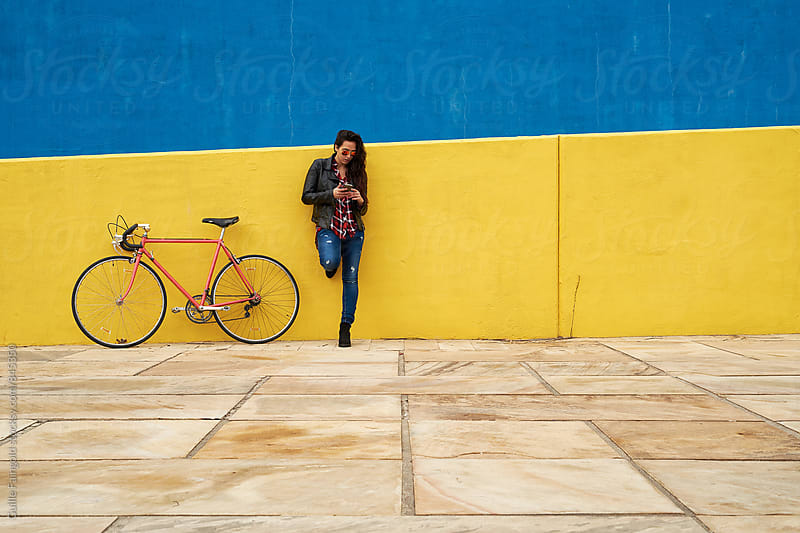 Young woman standing beside his bicycle using her smartphone by Guille Faingold for Stocksy United