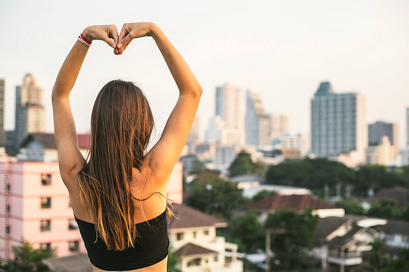 Young woman making a heart sign with her body.  by Jovo Jovanovic for Stocksy United