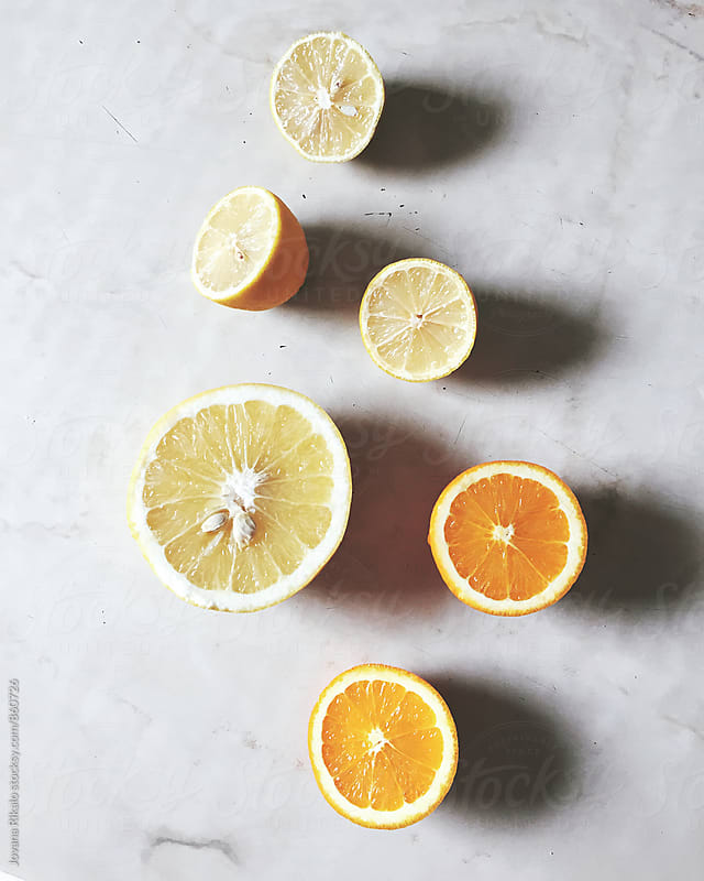Orange, grapefruit and lemon pieces on a table by Jovana Rikalo for Stocksy United