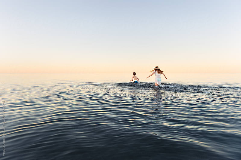 Boy and girl running in shallow calm water at dusk by Angela Lumsden for Stocksy United