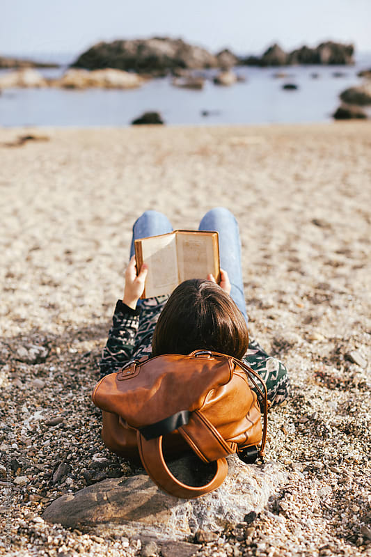 Back view of woman relaxing reading a book on the beach. by BONNINSTUDIO for Stocksy United