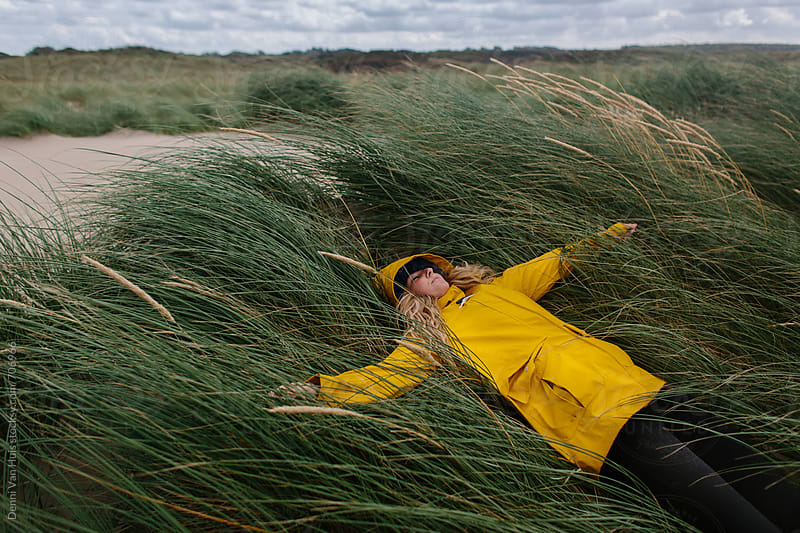 Woman hiding for the wind in the dunes while wearing a yellow raincoat by Denni Van Huis for Stocksy United