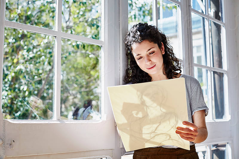Young Woman Sketching By Window by ALTO IMAGES for Stocksy United