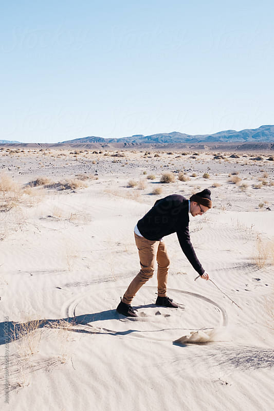 young man drawing circle in the sand in desert by Jesse Morrow for Stocksy United