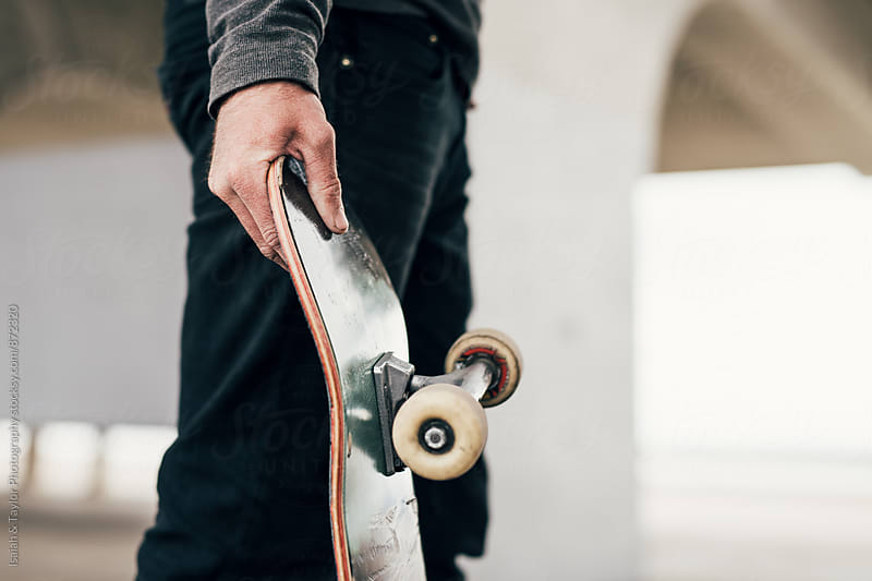 Hand holding skateboard by Isaiah & Taylor Photography for Stocksy United