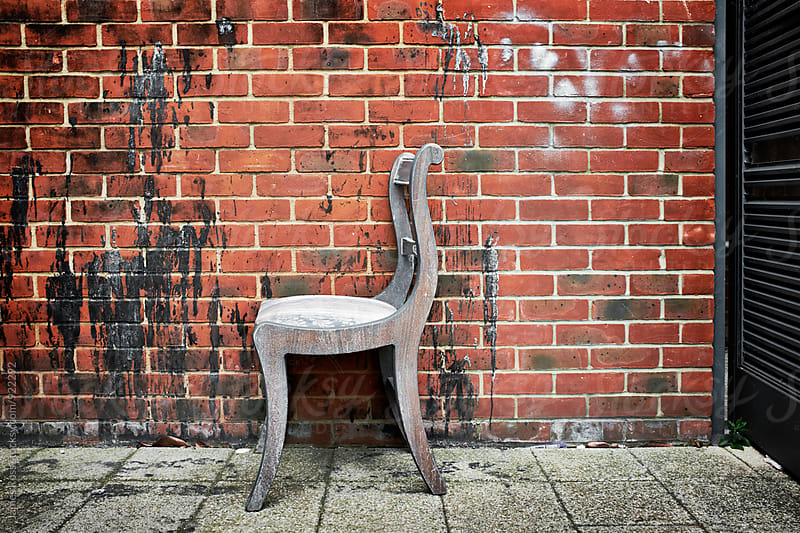 A chair left by a wall by James Ross for Stocksy United