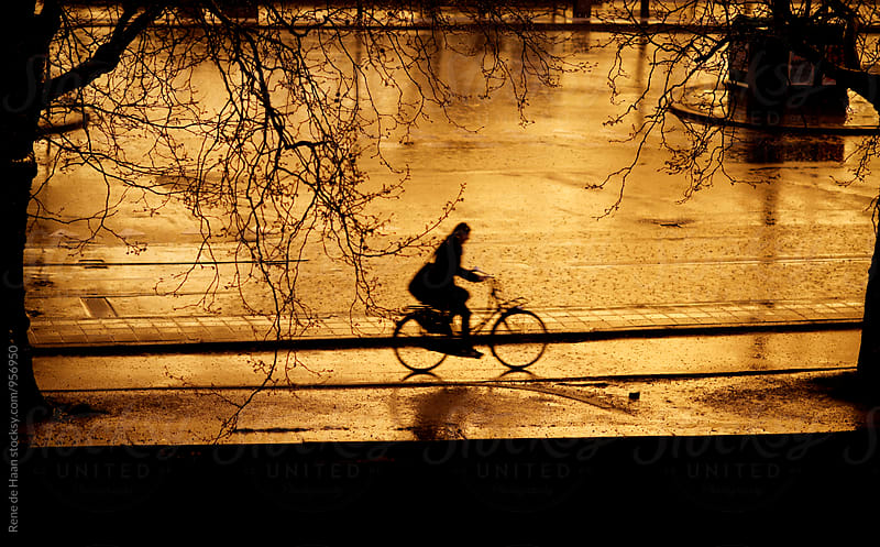 biking through the rain after sunset by Rene de Haan for Stocksy United