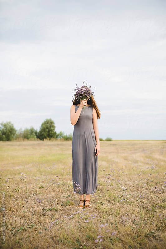 Young woman covering her face with flower bouquet by Jovana Rikalo for Stocksy United