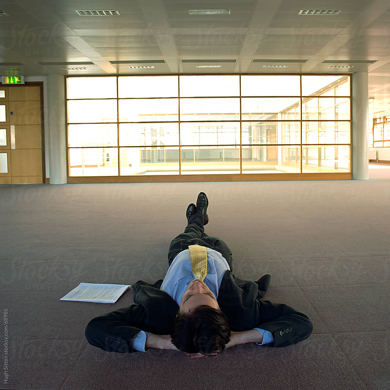 Businessman lying on floor of empty office building by Hugh Sitton for Stocksy United