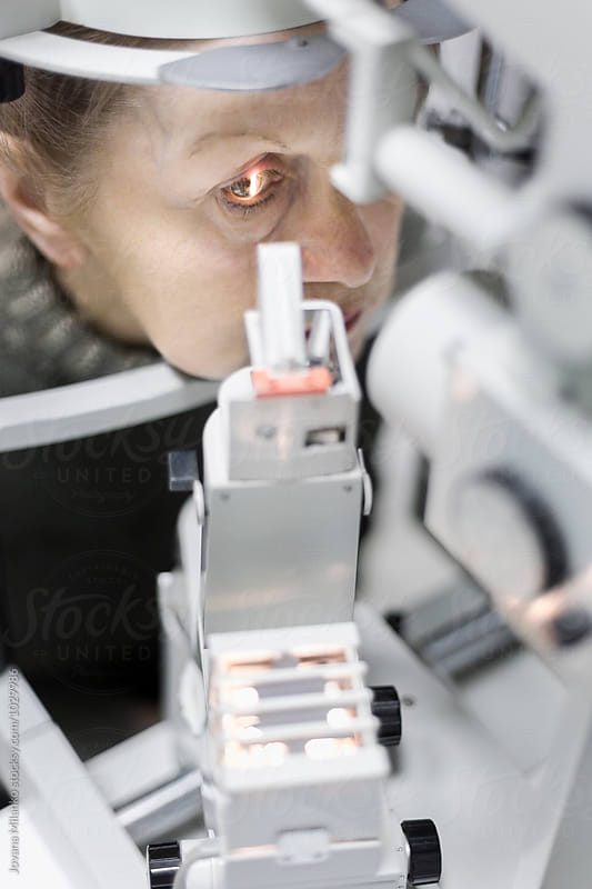 Senior woman checking her eyesight at ophthalmology clinic by Jovana Milanko for Stocksy United