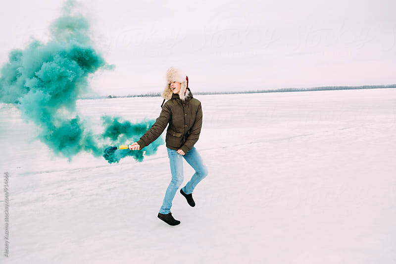young man play with green smoke bomb by Alexey Kuzma for Stocksy United