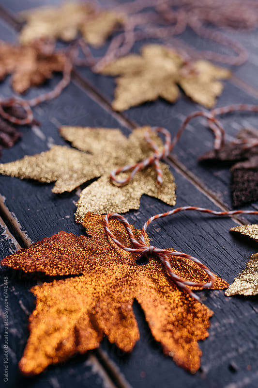 Fall leaves covered with golden glitter by Gabriel (Gabi) Bucataru for Stocksy United