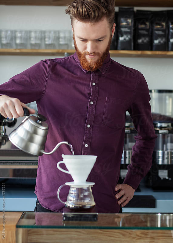 Portrait of young man making coffee at a cafe. by W2 Photography for Stocksy United