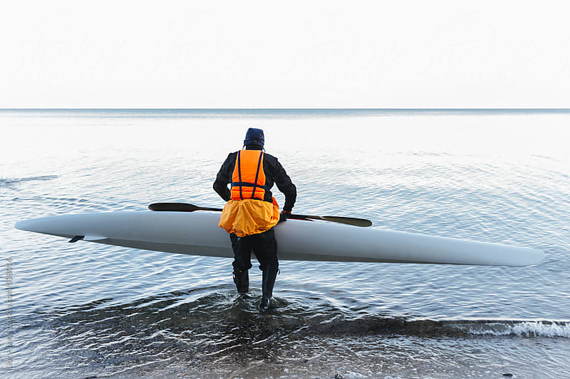 Man carrying kayak into the sea by Lior + Lone for Stocksy United