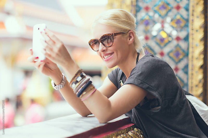 Smiling Tourist Taking Photos With Her Mobile Phone by Lumina for Stocksy United