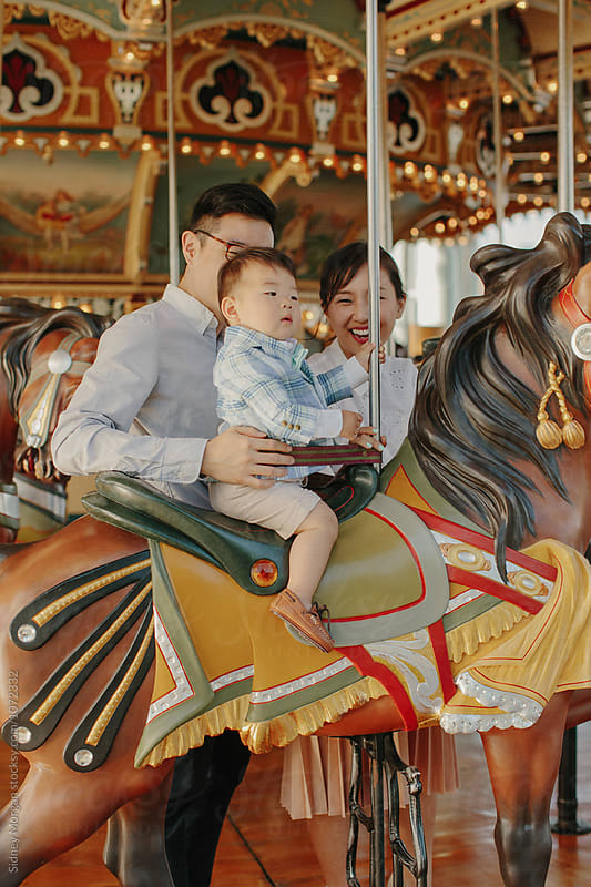 Young Family on Carousel by Sidney Morgan for Stocksy United