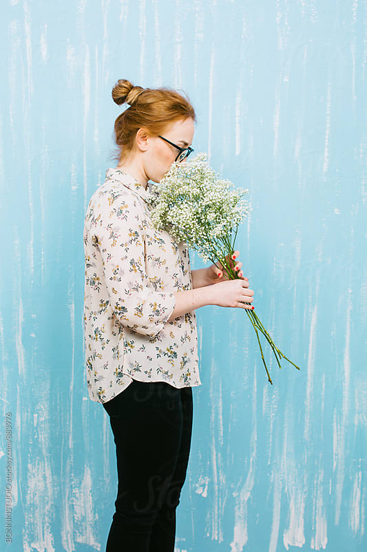 Side view of a ginger woman smelling a bouquet of flowers. by BONNINSTUDIO for Stocksy United