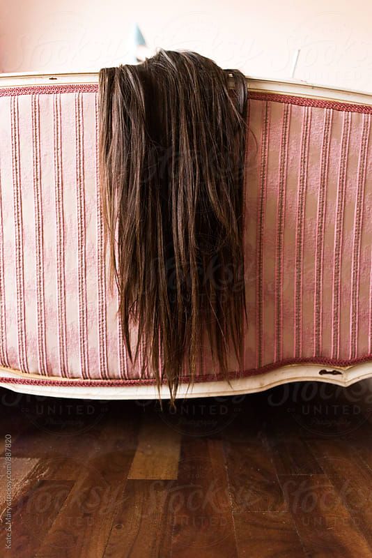 Close up of hair on vintage bed by Kate & Mary for Stocksy United
