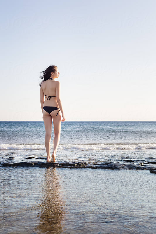 Young Woman Looks out to Sea Standing on a Rocky Shore by Helen Sotiriadis for Stocksy United