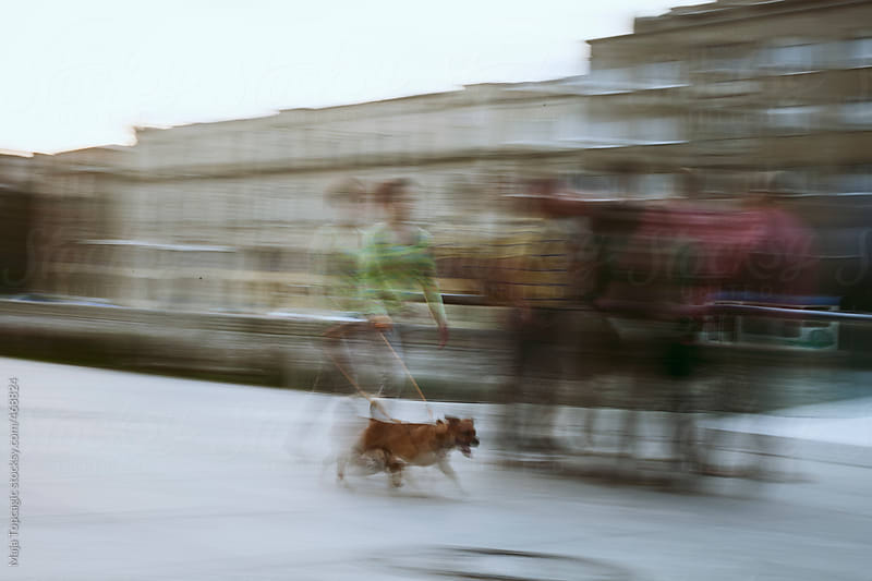 Woman walking a dog on the street by Maja Topcagic for Stocksy United