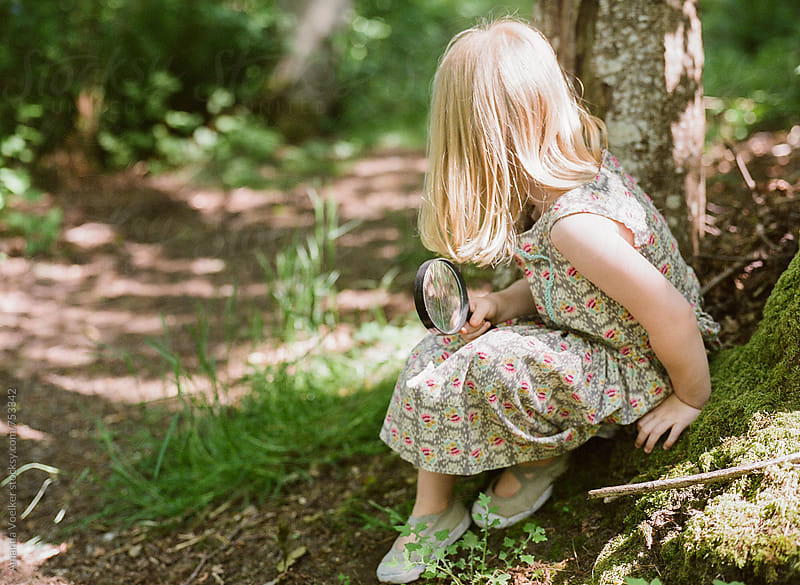 Young Girl Sits by a forest path with a spy glass by Amanda Voelker for Stocksy United
