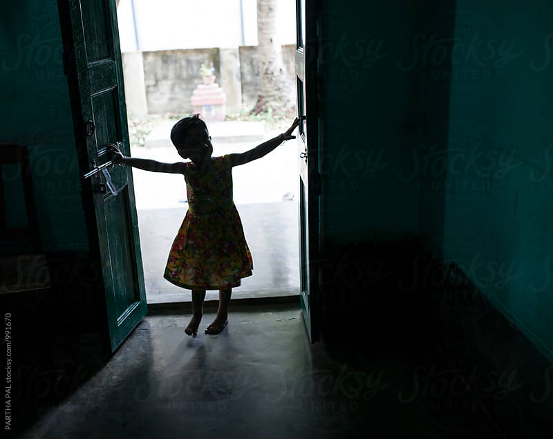 A little girl entering through a door by PARTHA PAL for Stocksy United