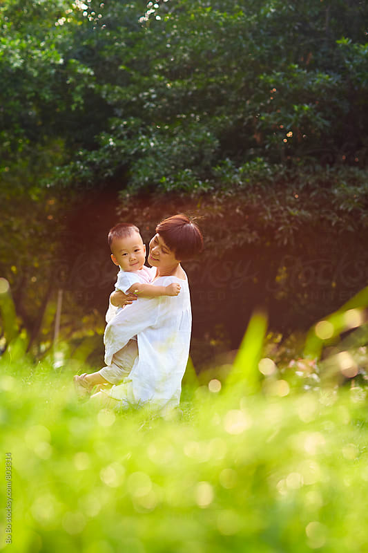 asian mother and son outdoor in the sunny park by Bo Bo for Stocksy United