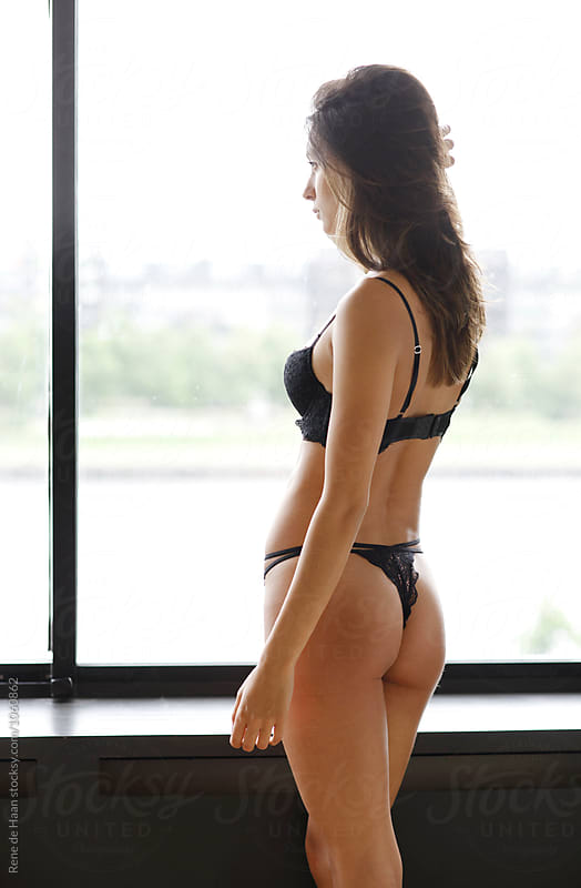 young woman in black lingerie, looking out window by Rene de Haan for Stocksy United