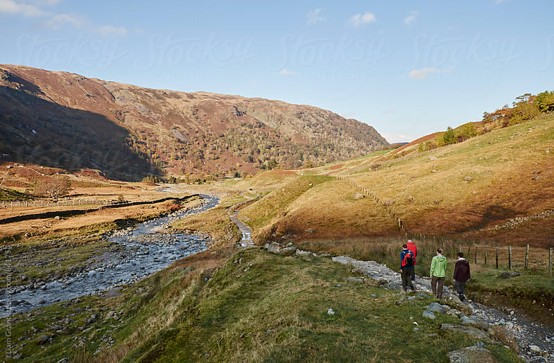 Group of people walking in a mountain valley. Seathwaite, Cumbria, UK. by Liam Grant for Stocksy United