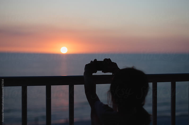 Silhouette of child taking a photo of the sun setting over the ocean from balcony by Amanda Worrall for Stocksy United