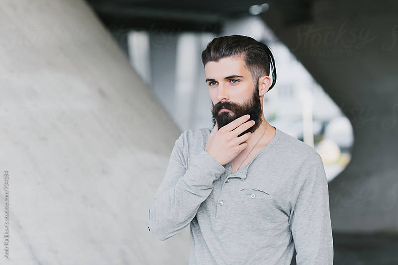 Pensive bearded man looking into the distance by Amir Kaljikovic for Stocksy United