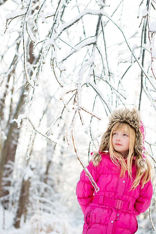 Little Girl Looking at Cold Winter Woods With Frozen Ice and Snow by JP Danko for Stocksy United