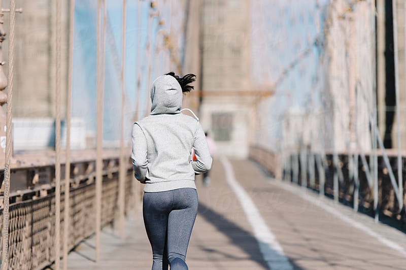 Young woman jogging on the Brooklyn Bridge in the morning.  by Cameron Whitman for Stocksy United