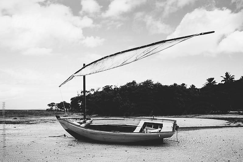 Small sailboat on beach on low tide, near Salvador, Bahia, Brazil by Paul Edmondson for Stocksy United